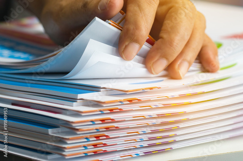 Obraz na plátně  Businessman hands searching unfinished documents stacks of paper files on office desk for report papers, piles of sheet achieves with clips on table, Document is written, drawn,presented