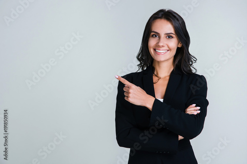 You need to look here! Beautiful young businesswoman pointing away and looking at camera with smile while standing against white background