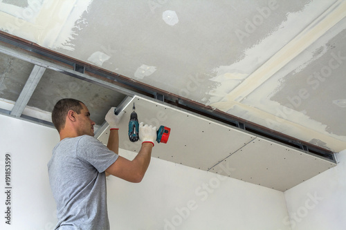 Construction worker assemble a suspended ceiling with drywall and fixing the drywall to the ceiling metal frame with screwdriver Canvas Print