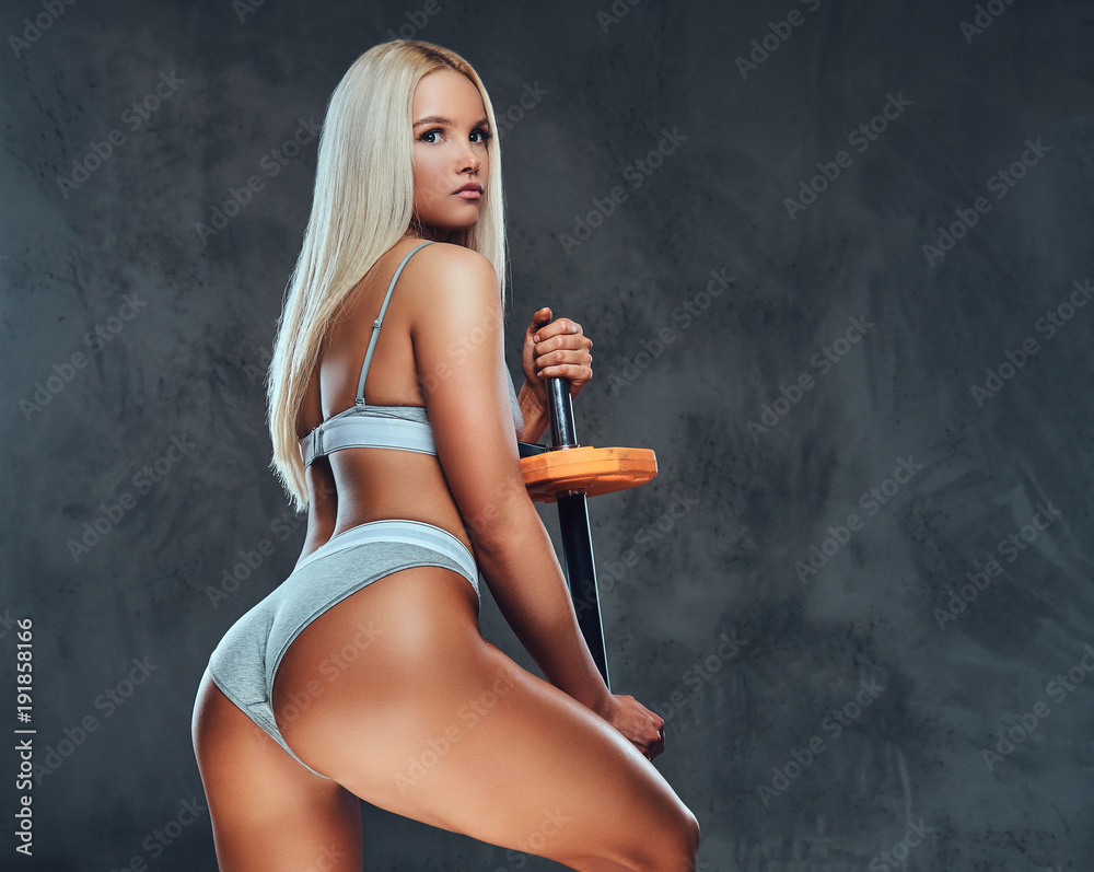 Fototapety, obrazy: Sexy blonde fitness model posing with a barbell