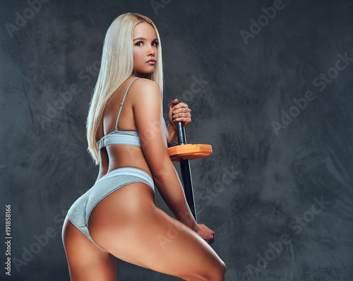 Fotografie, Obraz  Sexy blonde fitness model posing with a barbell