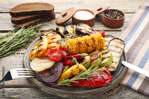 Photo Stands Grill / Barbecue Grilled vegetable on brown cutting board with knife and fork