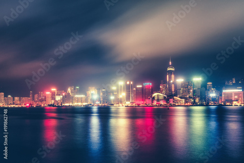 Scenic nighttime skyline of Hong Kong island, China, with skyscrapers and city illuminations. Victoria harbor at night. Multicolored travel background.