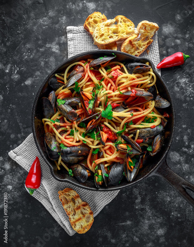 Poster Klaar gerecht Homemade Pasta Spaghetti with mussels, tomato sauce, chilli and parsley in rustic skillet, pan. sea food meal