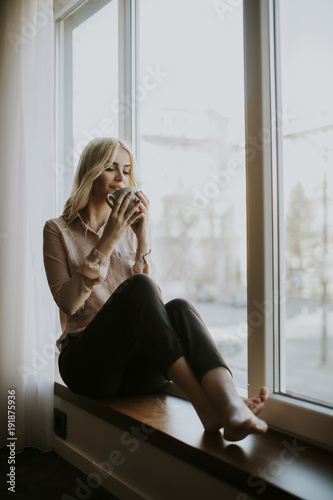 Photo  Blonde young woman drinking coffee by window