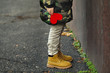 canvas print picture - Lonely little child with red paper heart standing near wall outdoors. Autism concept