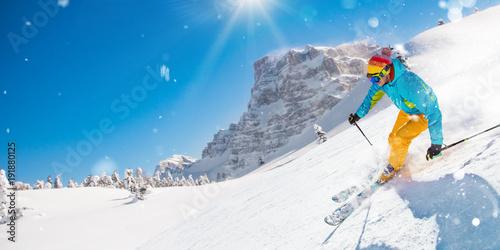Fotobehang Wintersporten Skier on piste running downhill in beautiful Alpine landscape. Blue sky on background.