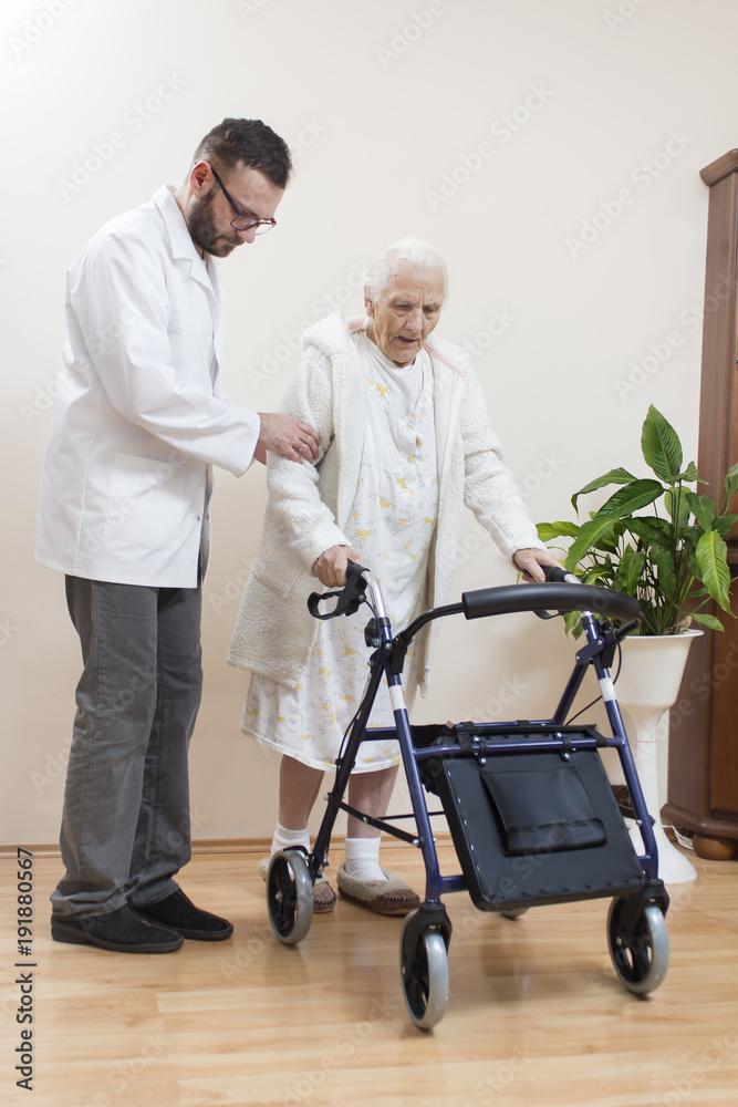 Fototapeta 2.Staruszka uczy się chodzić przy pomocy balkonika rehabilitacyjnego  przy asekuracji lekarza.