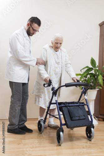 Fototapeta 2.Staruszka uczy się chodzić przy pomocy balkonika rehabilitacyjnego  przy asekuracji lekarza. obraz