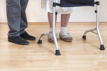 4.Nogi bardzo starej kobiety w białych skarpetkach i pantoflach. Staruszka uczy się chodzić przy pomocy chodzika rehabilitacyjnego.