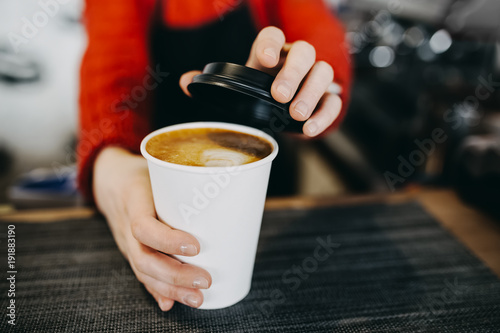 Montage in der Fensternische Kaffee Barista in apron is holding in hands hot cappuccino in white takeaway paper cup. Coffee take away at cafe shop