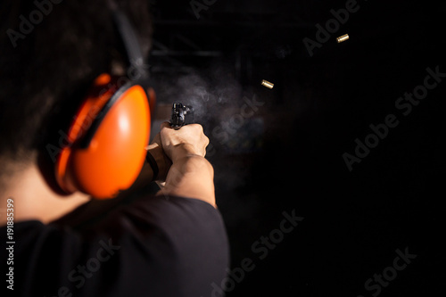 Papel de parede man shooting pistol gun, fire bullet, and wear orange ear cover in shooting rang