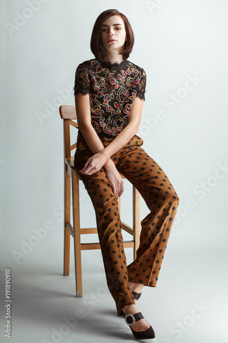 vintage fashion woman sitting on wooden chair on white studio background Wall mural