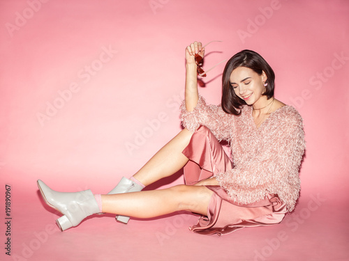 woman fashion model in pink sunglasses, sweater and skirt sitting on pink background