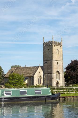 Fotografie, Obraz Late spring sunshine on colourful narrowboats moored near St Marys Church on the