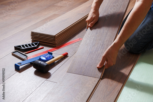 Man Laying Laminate Flooring Closeup On Male Hands