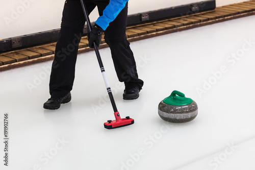 Foto curling sport - player with broom sweeping the ice before stone