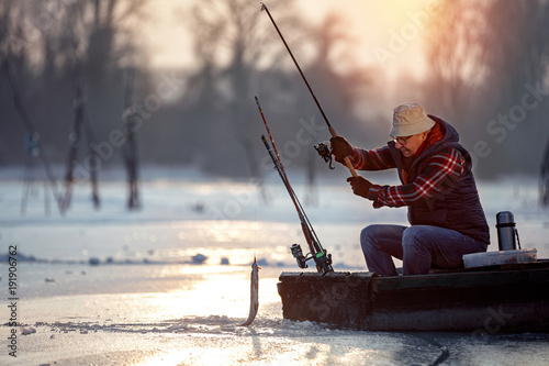 fisherman fishing on ice at the sunrise