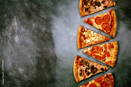 Foto op Canvas Pizzeria Slices of pizza with different toppings on a dark textured background