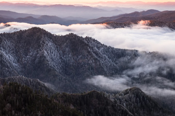 Fototapeta Popularne From a viewpoint high in the Great Smokey Mountains National Park stretches a line of mountain ridges to the horizon. It is sunrise and the sky is orange. Low clouds fill the valleys. Misty and foggy