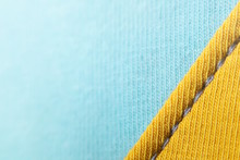 Close-up Of Seamded Up Fabrics In Two Pastel Tones - Yellow And Light Blue With Grey Seam - Visible Weave - Trendy Decorative Background With Copy Space For Text