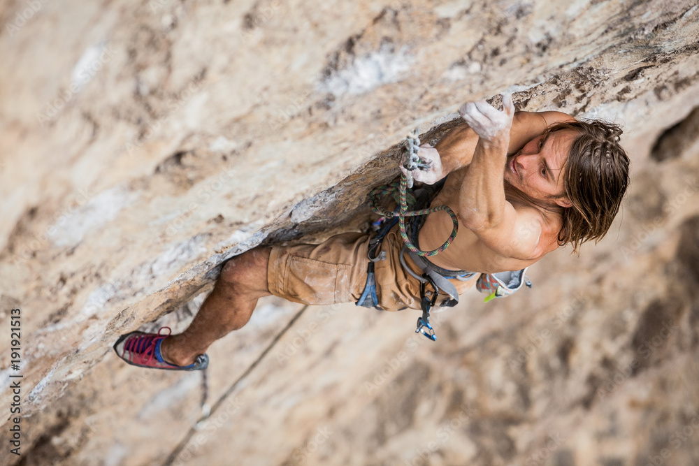 Fototapety, obrazy: shirtless male climber working hard to lead up a rock wall