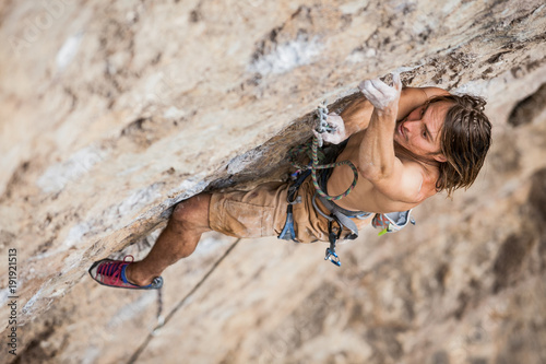shirtless male climber working hard to lead up a rock wall Fototapeta