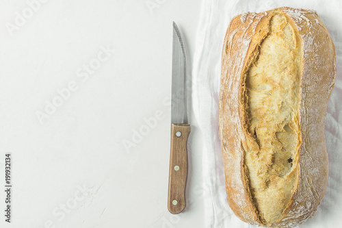 Freshly Baked Hand Crafted Rustic Bread Loaf on White Linen Towel with Knife on Textured Concrete Tabletop. Minimalist Japanese Authentic Style. Lifestyle Photo. Mediterranean Cuisine. Menu Template