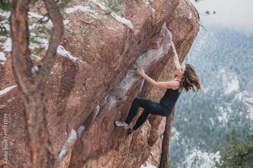Photo Female climber wearing black bouldering with snow and trees in the background