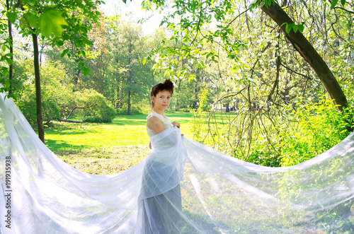 Fotografia  Oriental woman in long white dress Sunny afternoon strolls in the Park
