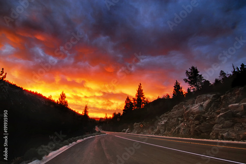 фотография A fiery sunset over a roadway in the Sierra Nevada mountains near Lake Tahoe
