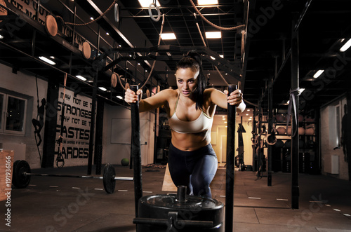 Fotografiet  Strong, beautiful  woman athlete pushing sleds with weights in gym