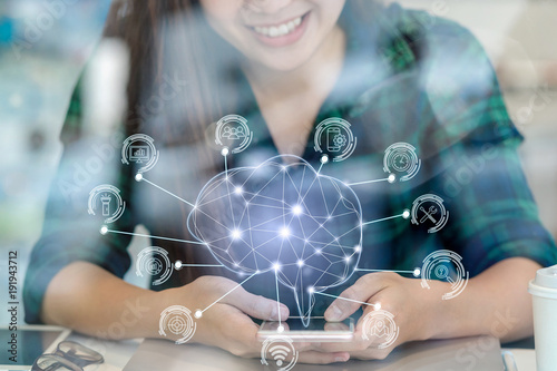 Obraz Polygonal brain shape of an artificial intelligence with various icon of smart city Internet of Things Technology over Asian businesswoman hand using the smart mobile phone,AI and business IOT concept - fototapety do salonu
