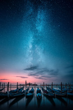 Gondolas In A Row And Chiesa Di San Giorgio Maggiore In Background Against Milky Way On The Sky