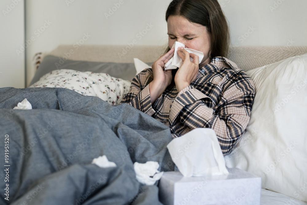 Fototapeta Sick woman sneezing in bed