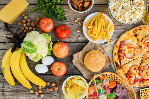 Fastfood and healthy food on old wooden background. Concept choosing correct nutrition or of junk eating. Top view.  © Victoria М