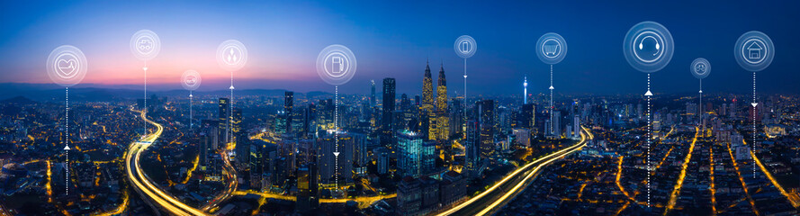 Fototapeta Panorama aerial view in the cityscape skyline with smart services and icons, internet of things, networks and augmented reality concept , early morning sunrise scene .