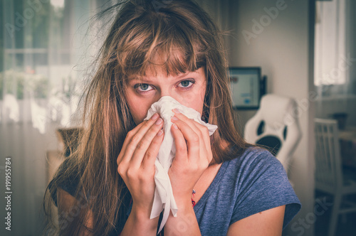 Fotografiet Sick woman with flu or cold sneezing into handkerchief