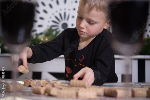 Little boy collects a pattern - a picture of wine corks