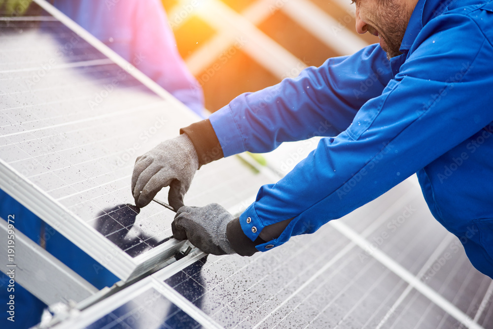 Fototapety, obrazy: Smiling male technician in blue suit installing photovoltaic blue solar modules with screw. Man electrician panel sun sustainable resources renewable energy source alternative innovation