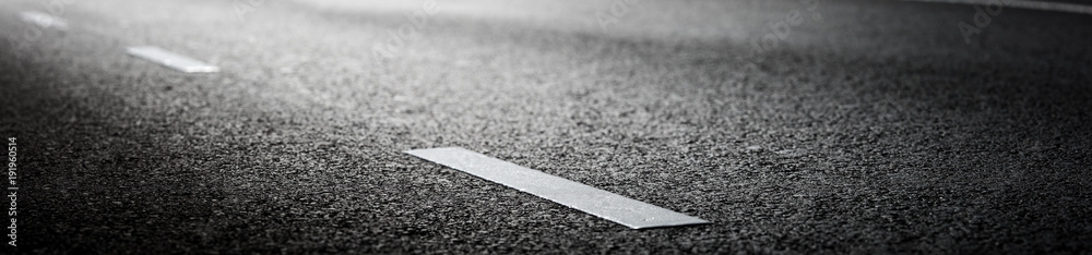 Fototapeta black asphalt road and white dividing lines