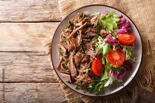 Delicious food: slow cooked pulled beef with fresh vegetable salad close-up. Horizontal top view from above