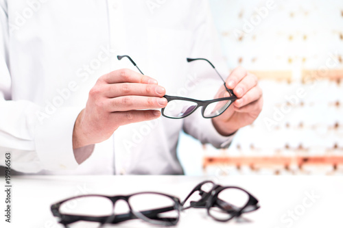 392a0d73d32 Optician in store holding glasses. Eye doctor with lenses. Professional  optometrist in white coat with many eyeglasses. Shop interior.