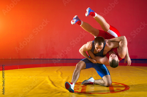Photo  Two young men in blue and red wrestling tights are wrestlng and making a suplex