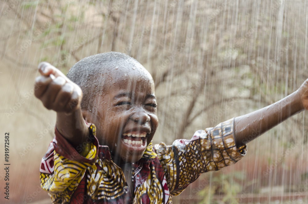 Fototapety, obrazy: Little Native African Boy Standing Outdoors Under the Rain (Water for Africa Symbol)