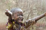 Fototapeta Łazienka - Little Native African Boy Standing Outdoors Under the Rain (Water for Africa Symbol)