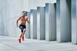 Leinwanddruck Bild - Handsome shirtless athlete jogging outside in modern urban setting