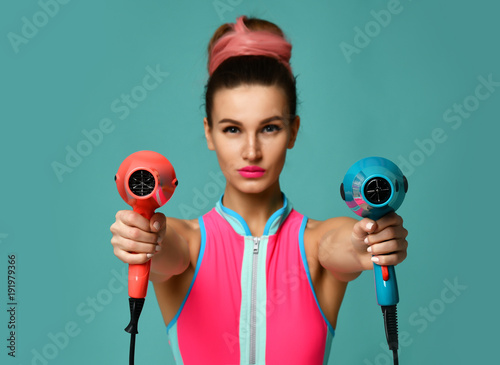 Papel de parede Happy young brunette woman with hair dryer on blue mint background