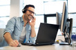 canvas print picture - Young smiling male call center operator doing his job with a headset.Portrait of call center worker at office.