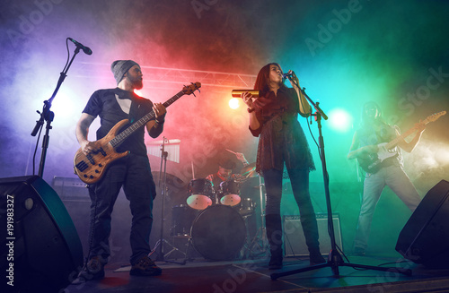 Fotografie, Obraz  Rock band performs on stage. Guitarist, bass guitar and drums.